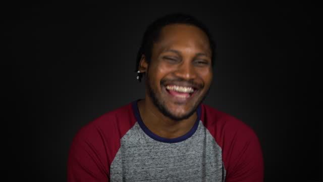 vídeos de stock e filmes b-roll de mid adult man laughing against black background - braided hair
