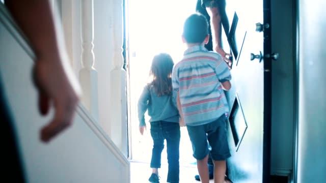 中期成人男性は、彼の家族との外出のために家を出ます - 建物入口点の映像素材/bロール