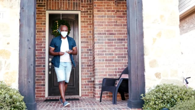 mid adult man leaves home wearing protective face mask during coronavirus pandemic - wreath stock videos & royalty-free footage