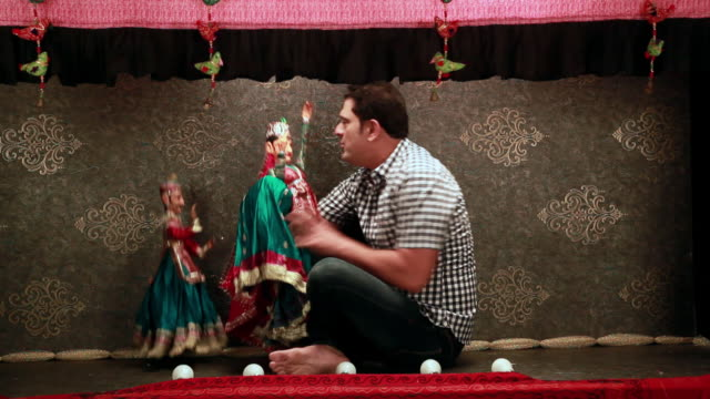 Mid adult man performing with puppets in a puppet show, Delhi, India