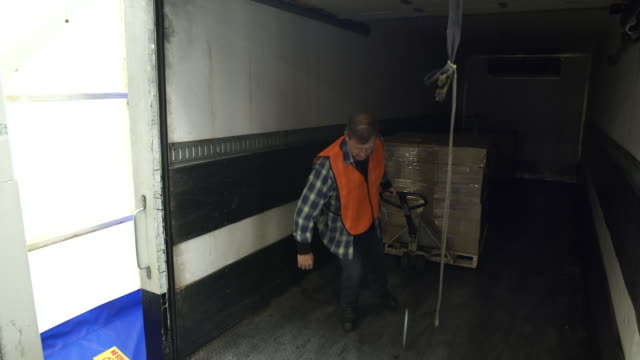 mid adult man pulling boxes into a warehouse - hubwagen stock-videos und b-roll-filmmaterial