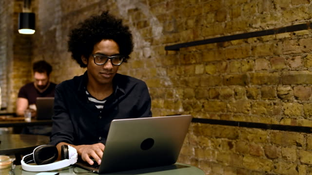 Mitte erwachsener Mann im Café Kopfhörer aufsetzen und mittels laptop
