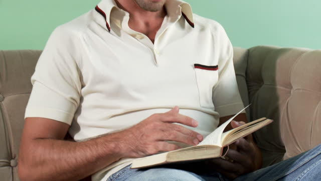 mid adult man reading book on sofa - hardcover book stock videos and b-roll footage