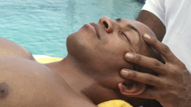 CU Mid adult man receiving face massage near pool, Arnos Vale, Tobago, Trinidad And Tobago