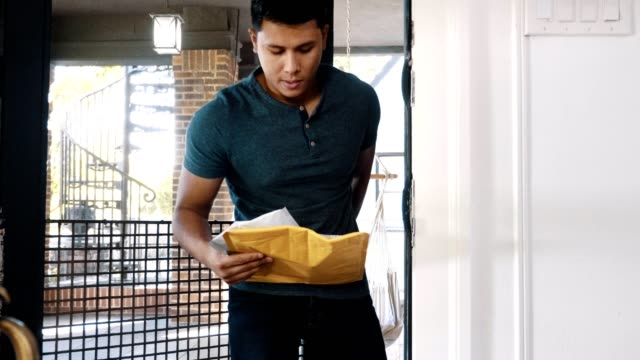 mid adult man retrieves a package from his front porch - reading mail stock videos & royalty-free footage