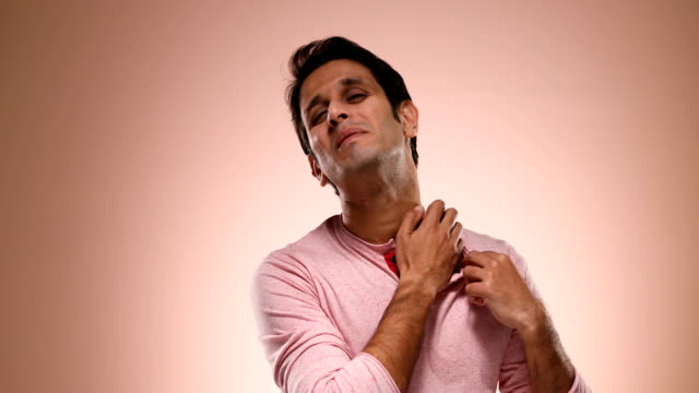 cu mid adult man scratching his neck against pink background / new delhi, delhi, india - allergy stock videos & royalty-free footage