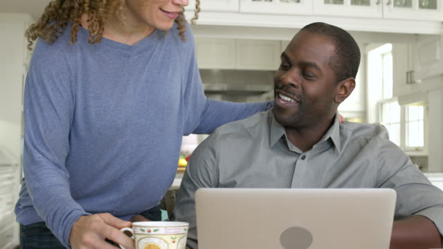 Mid adult man using a laptop in a kitchen