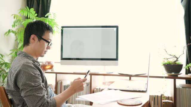 スマート フォンとラップトップを使用して 30 代の男性 - 30代点の映像素材/bロール