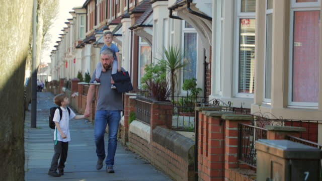 mid adult man walking down the street with his sons - newcastle upon tyne video stock e b–roll