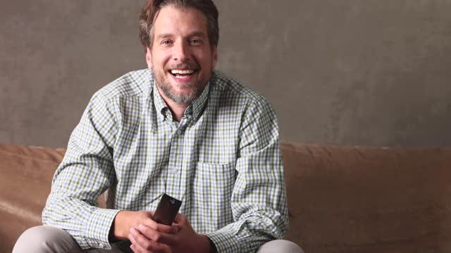 vídeos y material grabado en eventos de stock de hombre adulto medio viendo la televisión y sosteniendo el control remoto. - un solo hombre de mediana edad