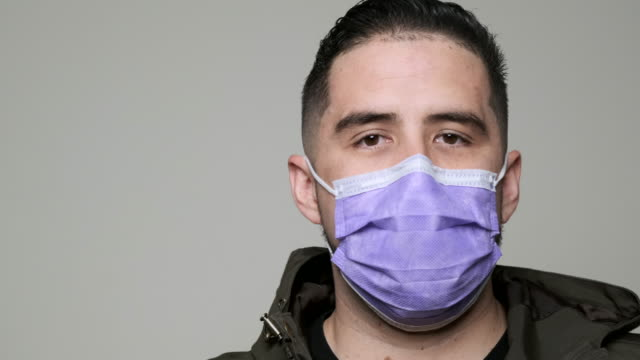 mid adult man wearing a medical mask looking at the camera - colombian ethnicity stock videos & royalty-free footage