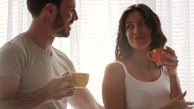 mid adult married couple rub noses as they enjoying their morning coffee together - mid adult couple stock videos & royalty-free footage