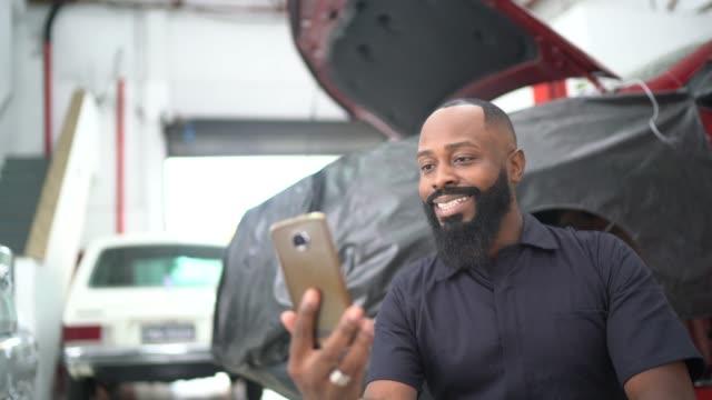 vídeos y material grabado en eventos de stock de hombres adultos medios haciendo un video chat en la reparación de automóviles - mecánico de coches