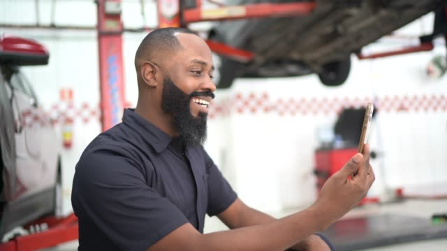 vídeos de stock, filmes e b-roll de homens adultos médios fazendo um bate-papo de vídeo no conserto de carros de automóveis - sentir a falta emoção