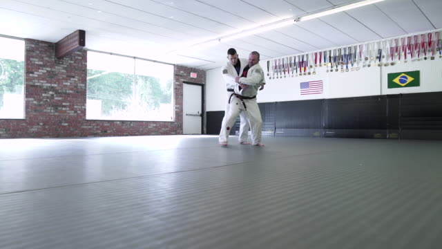 mid adult men practicing jiu-jitsu in a dojo - mid adult men stock videos & royalty-free footage