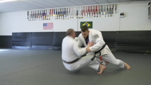 mid adult men practicing jiu-jitsu moves - mid adult men stock videos & royalty-free footage