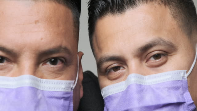 mid adult men wearing a medical mask looking at the camera - colombian ethnicity stock videos & royalty-free footage