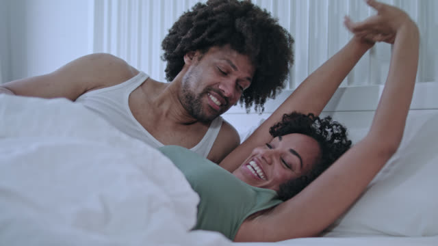 stockvideo's en b-roll-footage met mid adult mixed race dark-skinned love couple waking up together at home in white bed in the early morning and both are fit, in a good mood and full of energy for the starting working day. - dubbel bed
