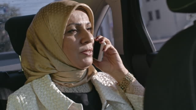 mid adult muslim woman talking on phone in back seat - mid adult stock videos & royalty-free footage