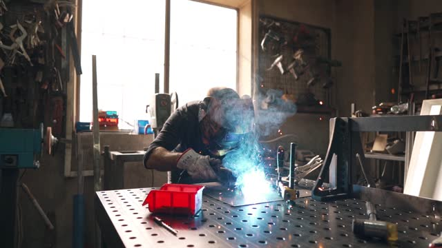 mid adult steel worker wearing welding helmet while using a torch to connect metal pipes - welding helmet stock videos & royalty-free footage