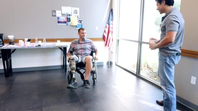 mid adult veteran in wheelchair shows stunts to friend - artificial limb stock videos & royalty-free footage