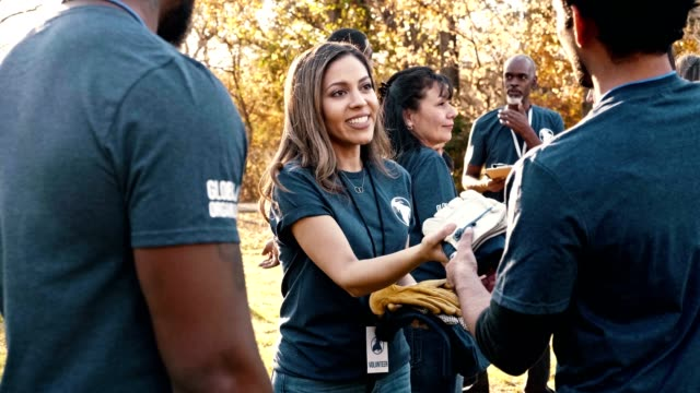 mid adult volunteer coordinator hands supplies to volunteers during cleanup event - leadership stock videos & royalty-free footage