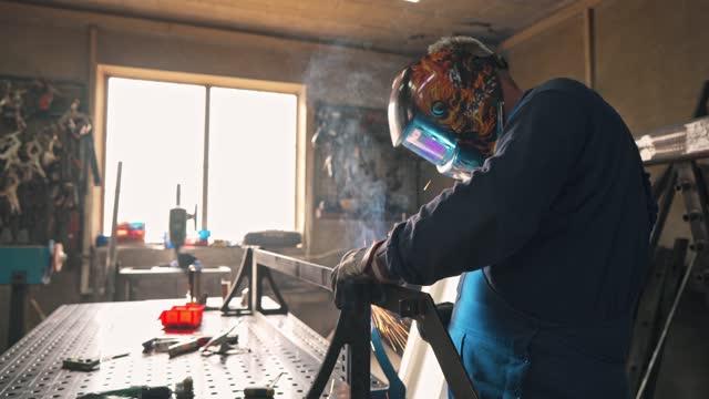 mid adult welder wearing welding helmet while working with welding torch at his workshop - welding helmet stock videos & royalty-free footage