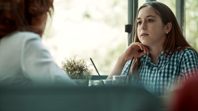 vídeos de stock e filmes b-roll de mid adult woman and teenage daughter in cafe - filha