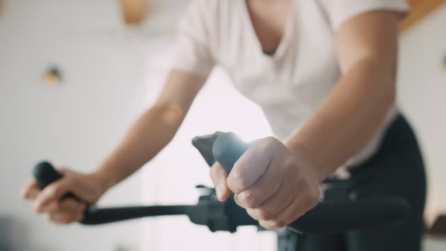 slo mo mid adult woman being exhausted after cycling on the exercise bike - home workout stock videos & royalty-free footage