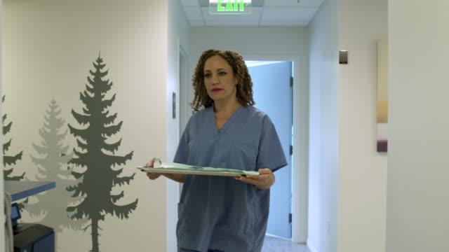 mid adult woman bringing medical equipment into an examination room - medical examination room stock videos & royalty-free footage
