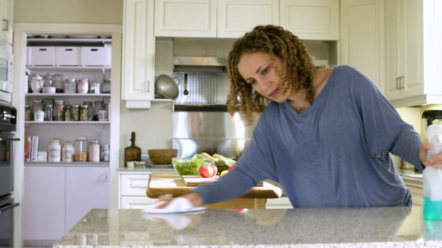 vídeos de stock e filmes b-roll de mid adult woman cleaning a kitchen counter - limpar