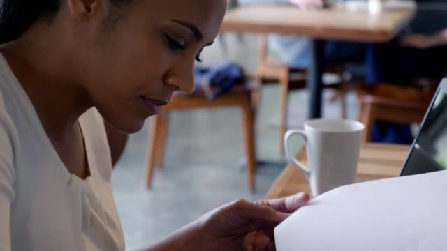 mid adult woman complete paperwork in coffee shop - application form stock videos & royalty-free footage