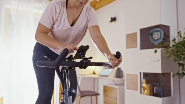 slo mo mid adult woman cycling on the exercise bike - exercise bike stock videos & royalty-free footage