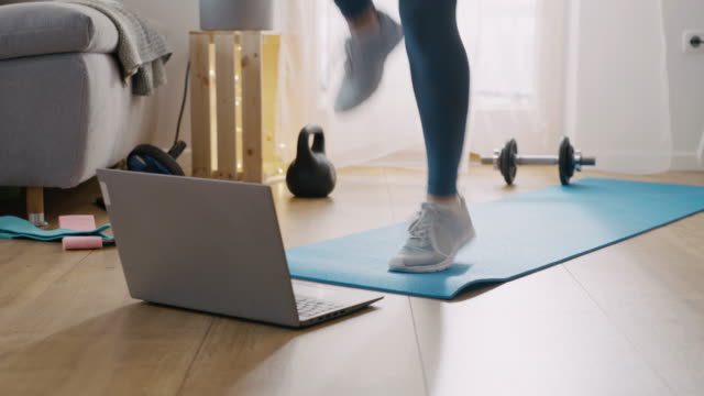 slo mo mid adult woman doing an online exercises at home - home workout stock videos & royalty-free footage