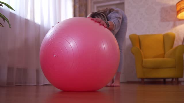 mid adult woman doing stretching exercise with fitness ball - fitness ball stock videos & royalty-free footage