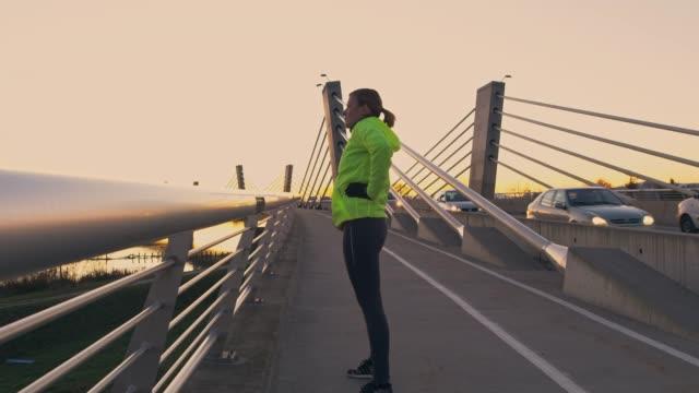 slo mo mitte erwachsene frau tun stretching übungen auf einer brücke in der abenddämmerung - einzelne frau über 30 stock-videos und b-roll-filmmaterial