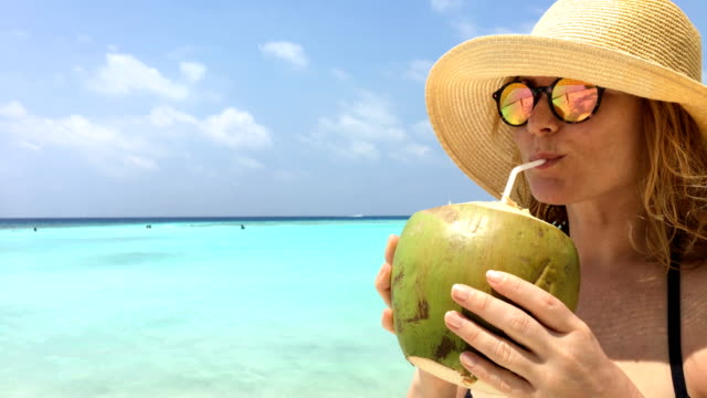 Mid Adult Woman Drinking Coconut Juice on a Beach on Tropical Island