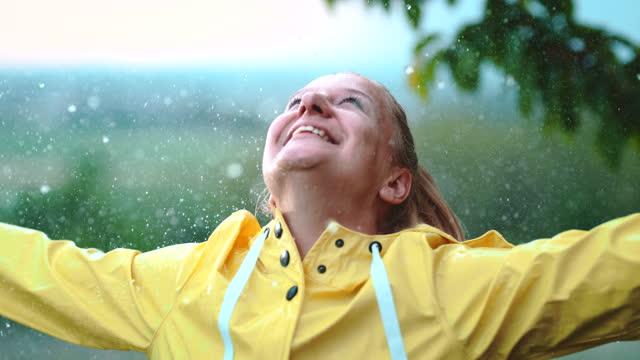 雨を楽しむスーパースローmoミッドアダルト女性 - レインコート点の映像素材/bロール
