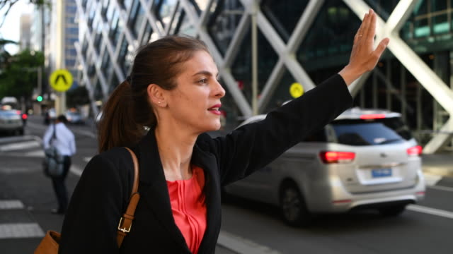 mid adult woman hailing a taxi in the city - taxi stock videos & royalty-free footage