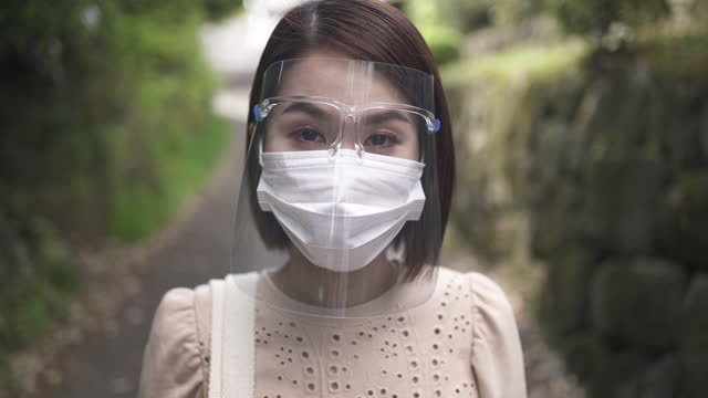 mid adult woman is out on the streets wearing a face shield and protective mask. - one mid adult woman only stock videos & royalty-free footage