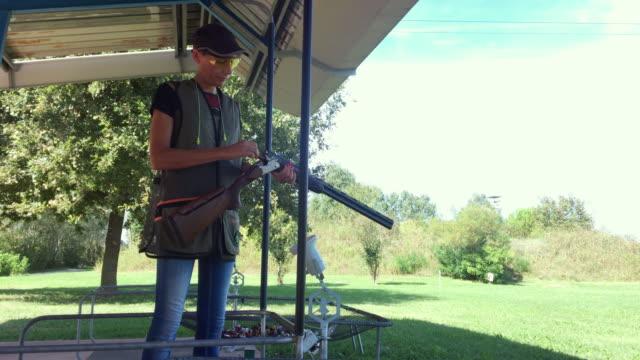 stockvideo's en b-roll-footage met mid adult woman leren hoe te schieten met shotgun op shooting range - jachtgeweer