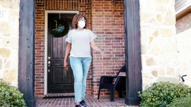 mid adult woman leaves home wearing protective face mask - wreath stock videos & royalty-free footage