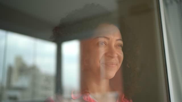 vídeos de stock, filmes e b-roll de mulher adulta média olhando pela janela em casa - sonhador