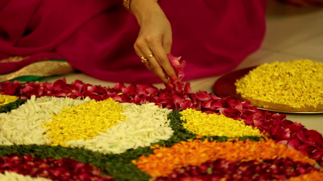 MS Mid adult woman making rangoli with flower during diwali festival