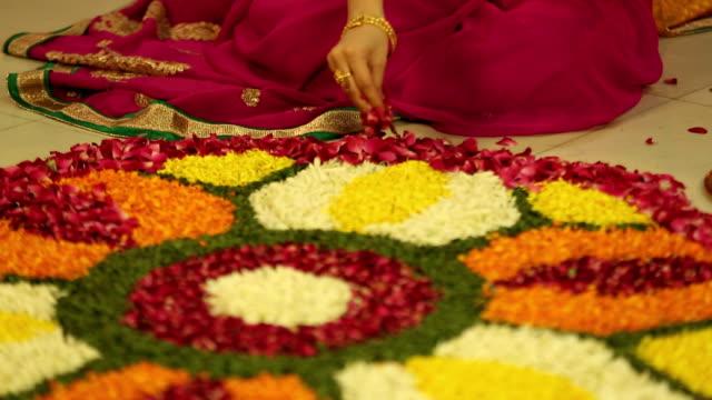 MS TU Mid adult woman making rangoli with flower during diwali festival