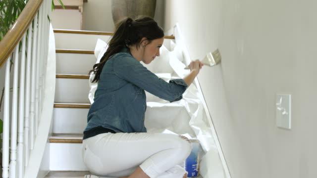 vídeos de stock e filmes b-roll de mid adult woman painting her home - pano de protecção