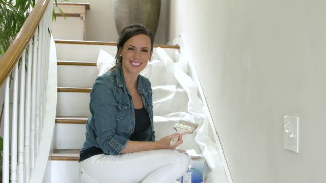 vídeos de stock e filmes b-roll de mid adult woman painting her home - one mature woman only