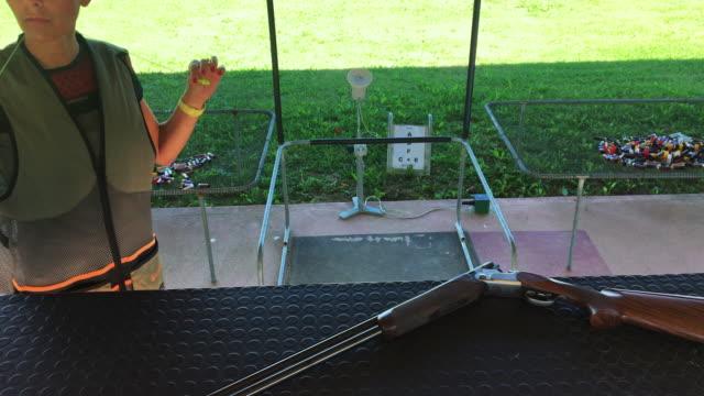stockvideo's en b-roll-footage met mid adult vrouw het oppakken van shotgun op shooting range - jachtgeweer