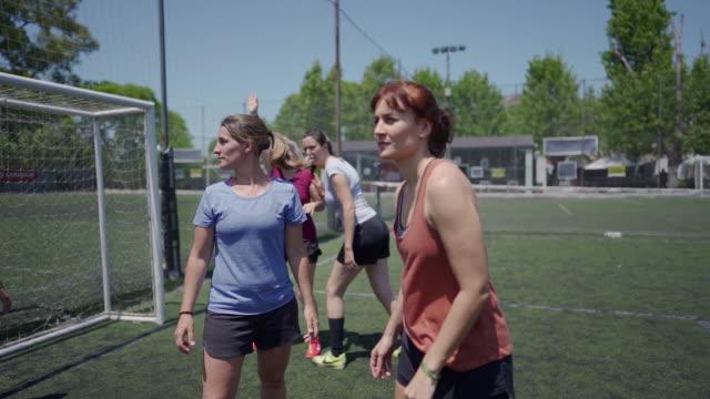 vidéos et rushes de femme adulte moyen jouant au football sur le terrain de football - hitting