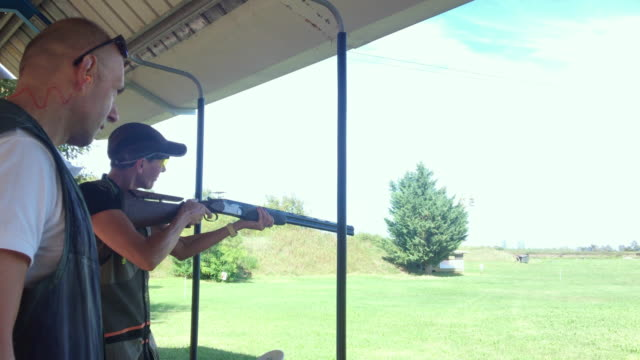 mid adult woman practicing skeet shooting on shooting range - tiro al piattello video stock e b–roll